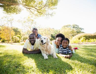Family in their yard outside with their dog.